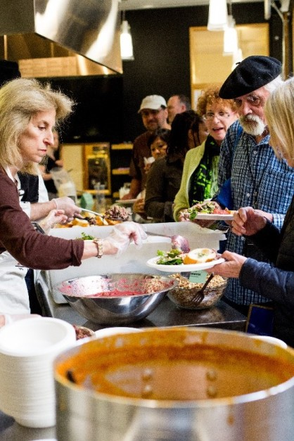 Volunteers serve food to Community Meal participants in the Atrium Kitchen.